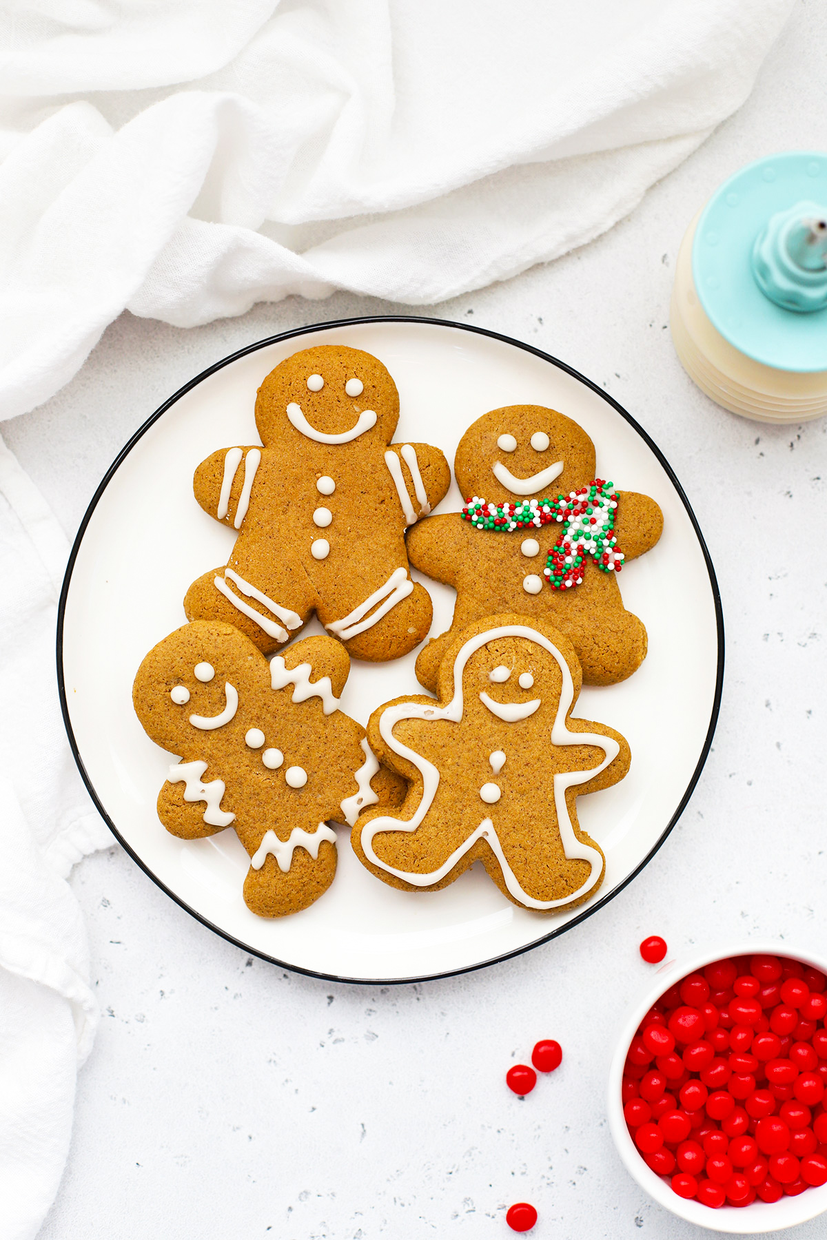 Overhead view of a plate of decorated gluten free gingerbread men cookies on a white background