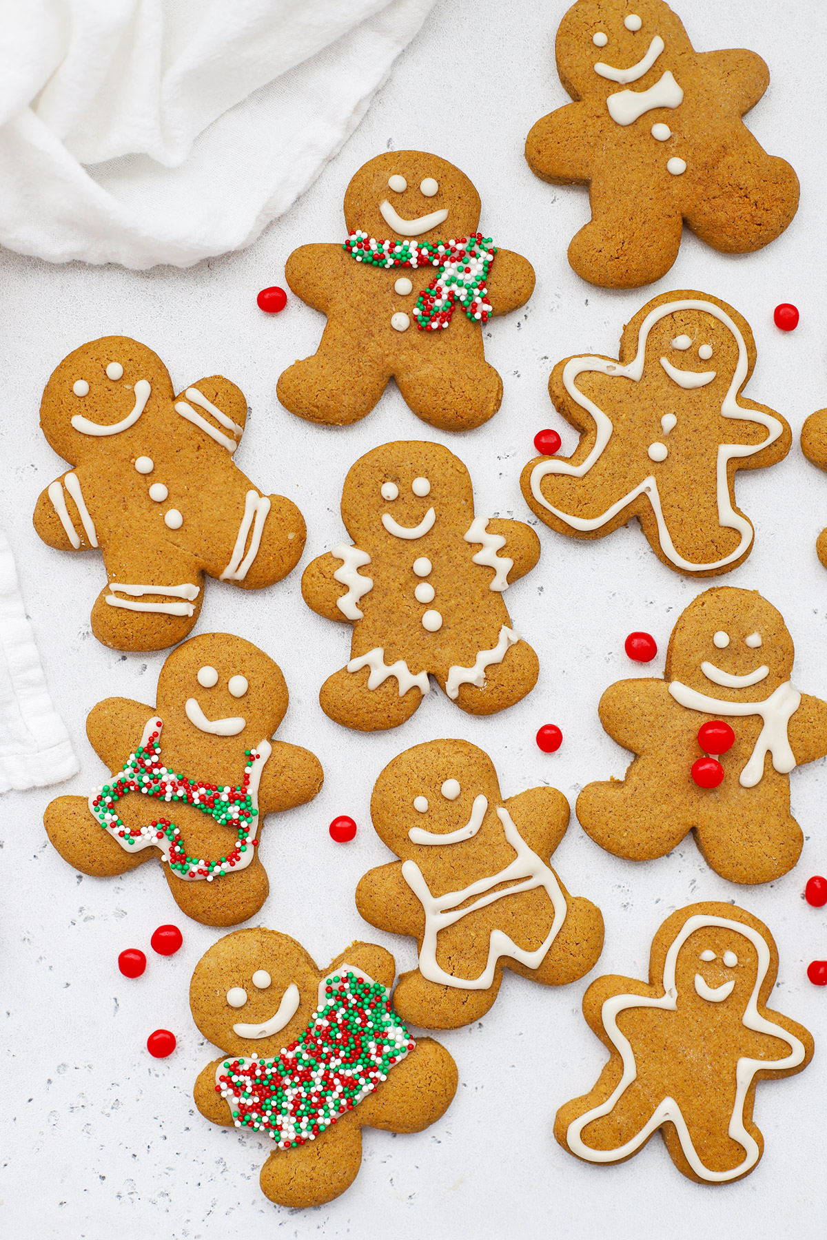 Overhead view of decorated gluten free gingerbread men cookies on a white background