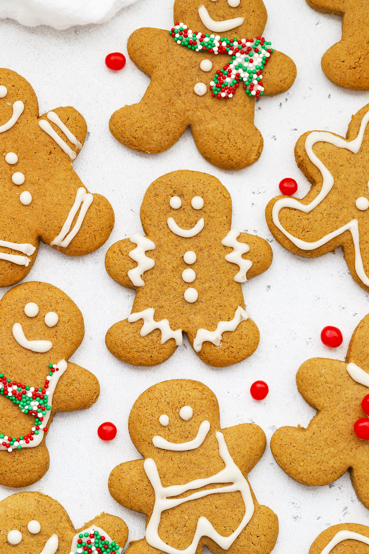 Close up Overhead view of decorated gluten free gingerbread men cookies on a white background