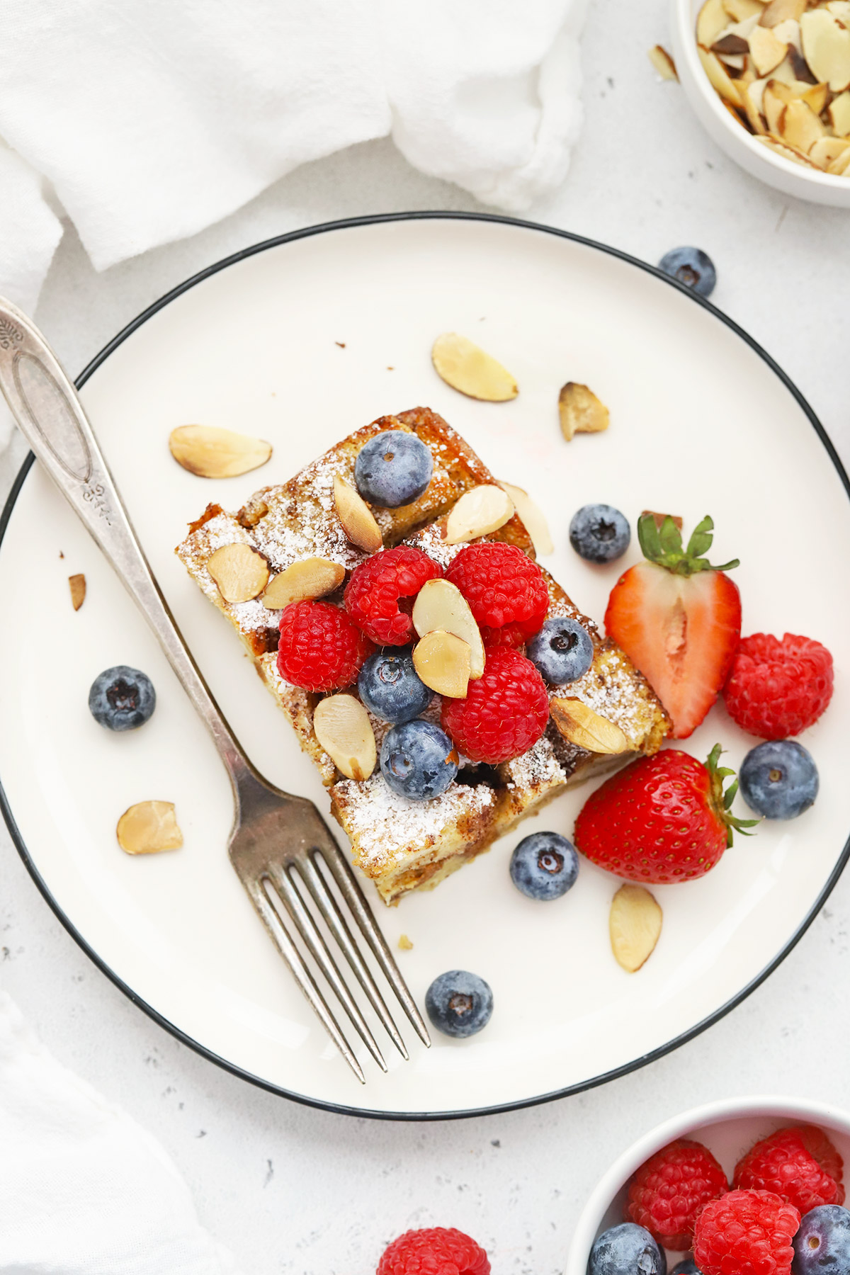 Overhead view of a slice of gluten-free french toast casserole on a white plate topped with berries and almonds