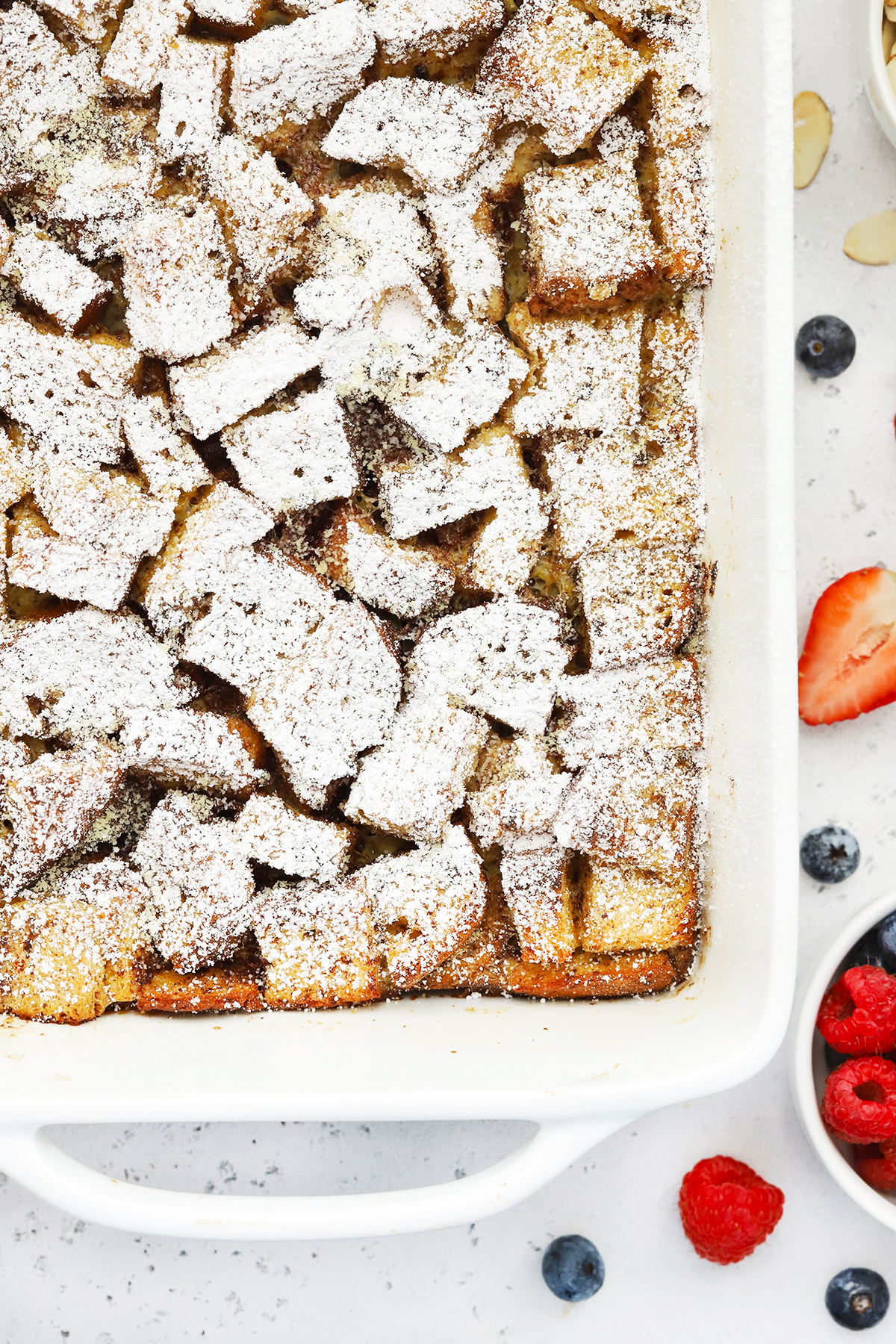 Close up overhead view of overnight gluten-free french toast casserole topped with powdered sugar
