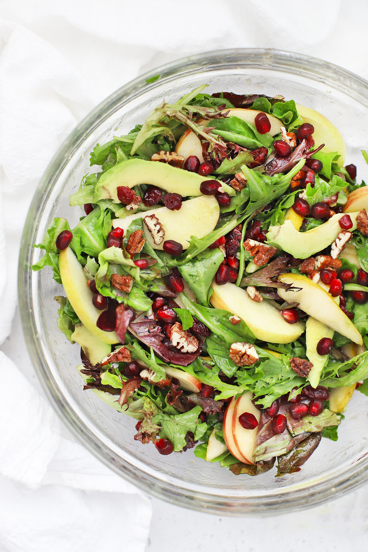 Overhead view of pear pomegranate salad in a glass bowl