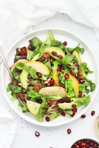 Overhead view of pear pomegranate salad on a white background