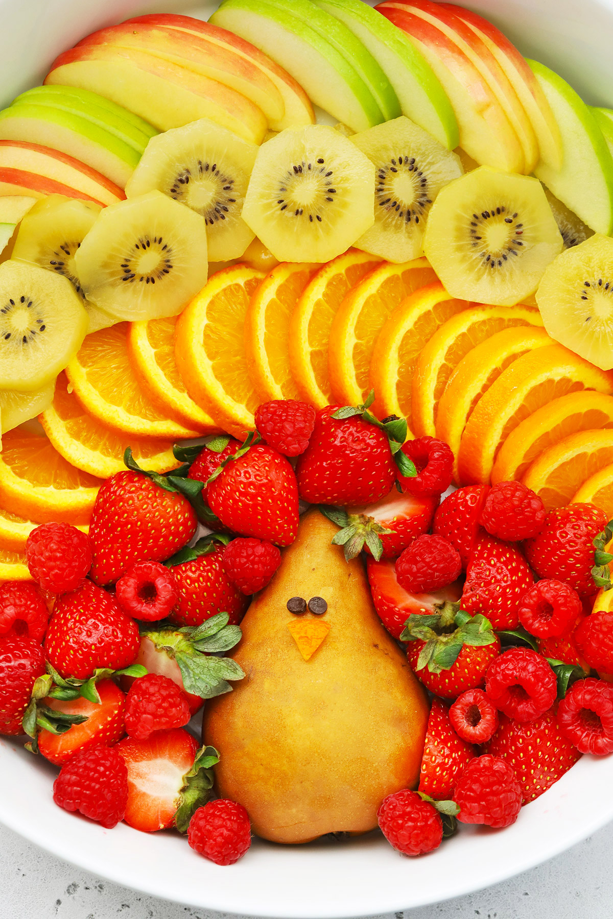 "Close up Overhead view of Thanksgiving Fruit Plate shaped like a turkey with text overlay that reads ""Cute + Easy Thanksgiving Turkey Fruit Plate: Simple + Fun + Adorable!"""