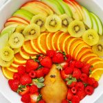 """Fruit plate arranged to look like a turkey with text overlay that reads """"Cute + Easy Thanksgiving Turkey Fruit Plate: Simple + Fun + Adorable!"""""""