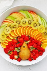 "Fruit plate arranged to look like a turkey with text overlay that reads ""Cute + Easy Thanksgiving Turkey Fruit Plate: Simple + Fun + Adorable!"""