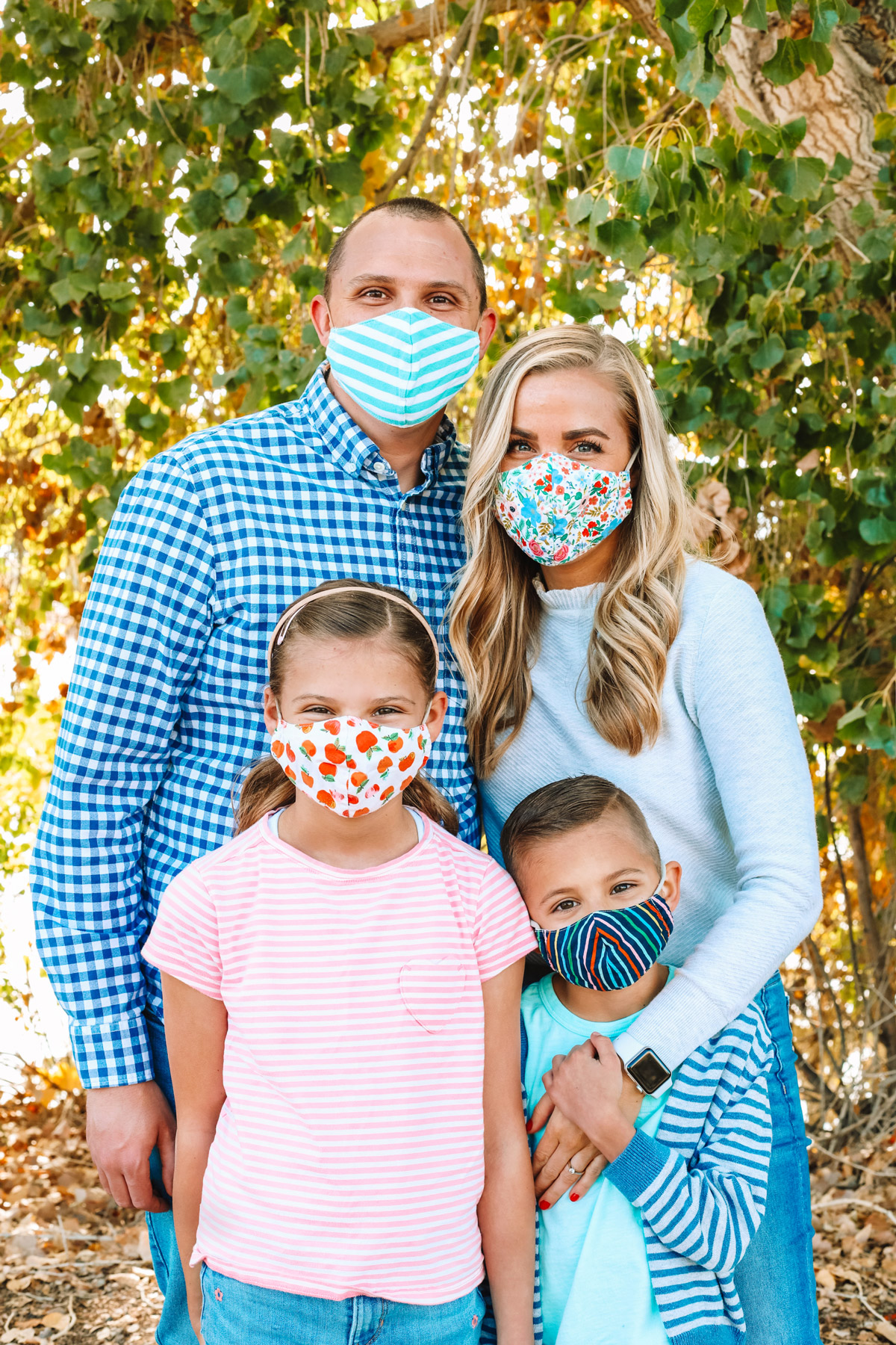 Emily from One Lovely Life with her family in front of a leafy background while wearing masks