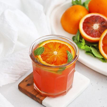 Front view of a blood orange mocktail garnished with fresh mint and blood oranges in the background