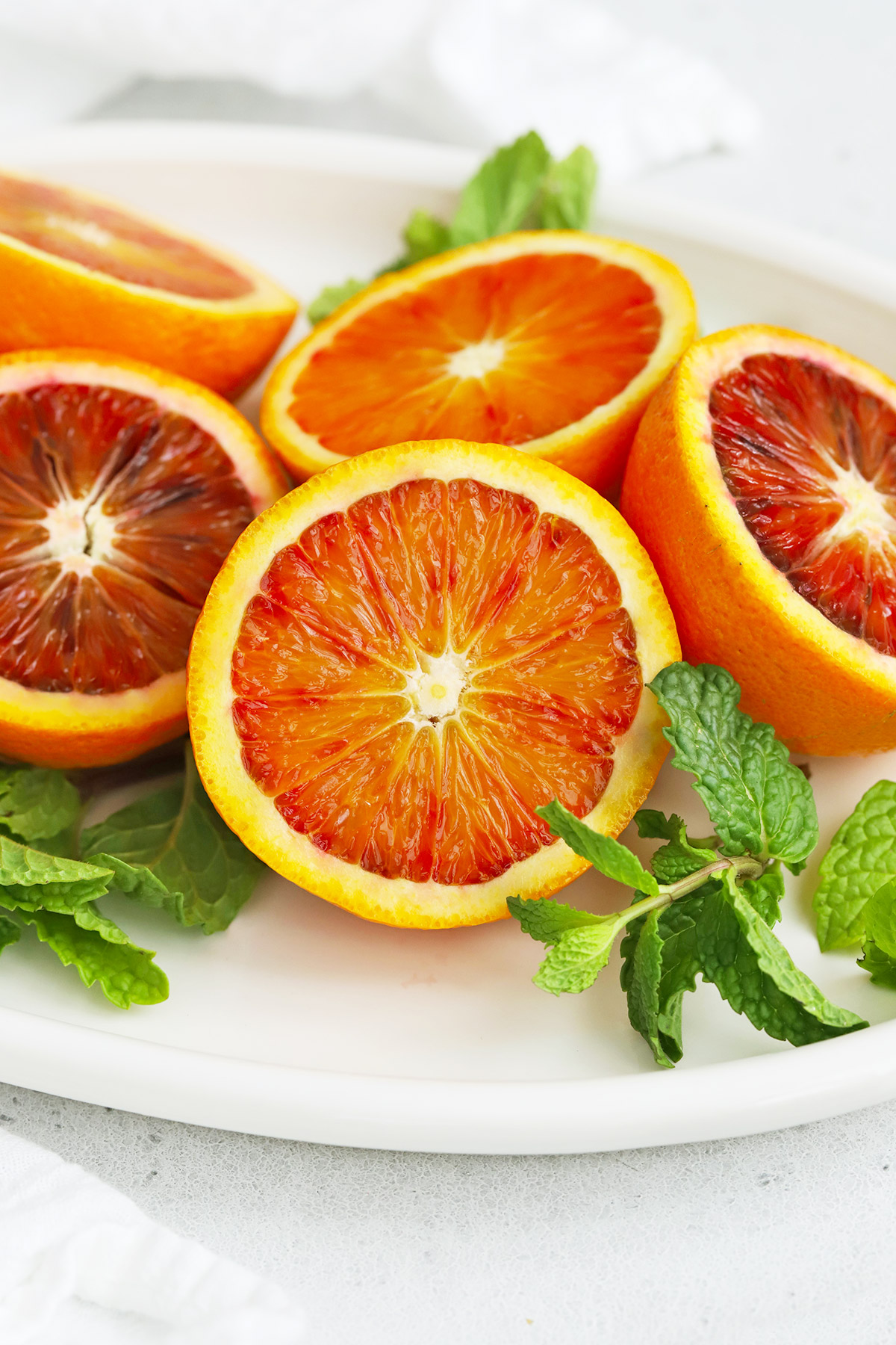 Halved blood oranges on a white platter with fresh mint