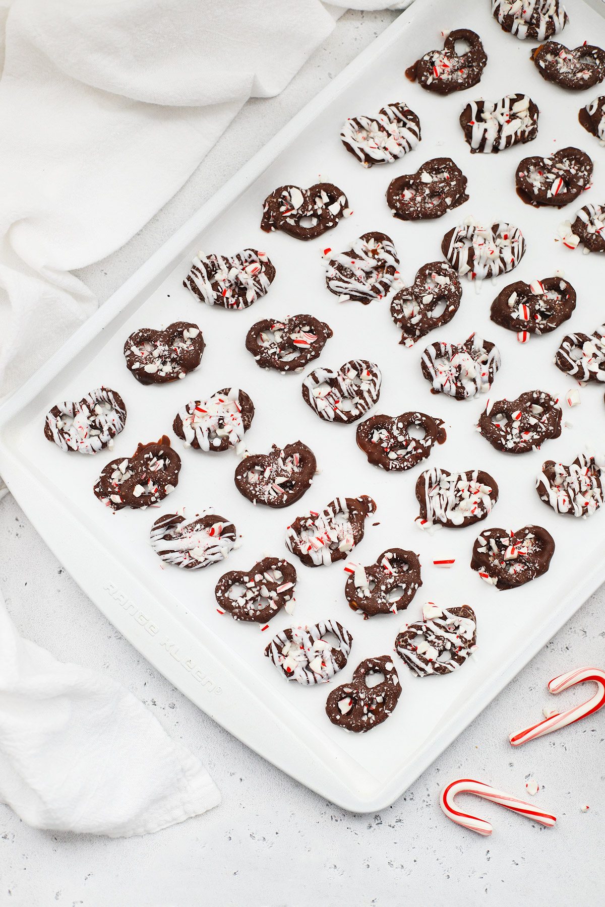 Overhead view of gluten-free chocolate peppermint pretzels covered with crushed candy canes cooling on a white baking sheet