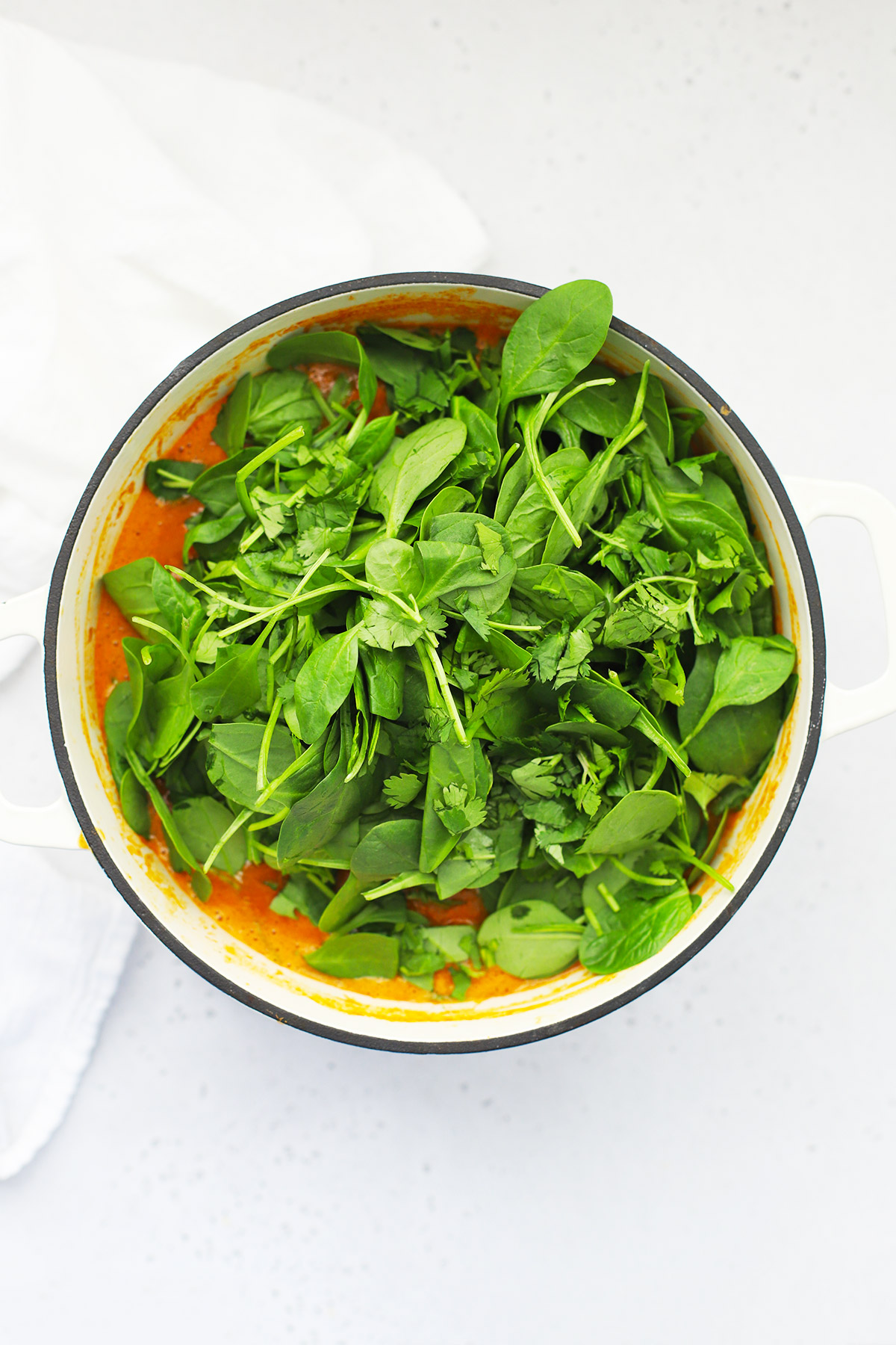 Overhead view of a white Dutch oven of curry lentil soup with fresh spinach and cilantro about to be stirred in.
