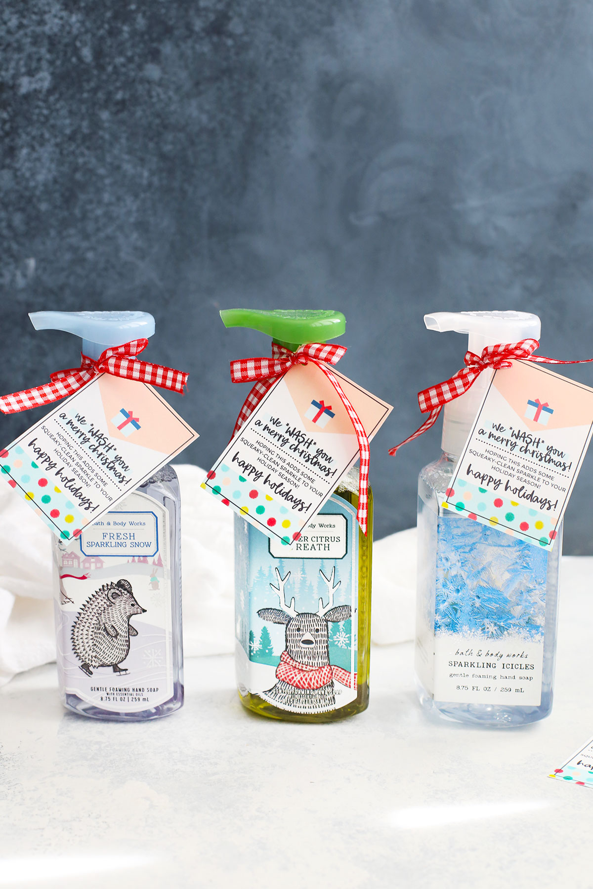 Front view of bottles of holiday soap with printable gift tags attached with ribbons