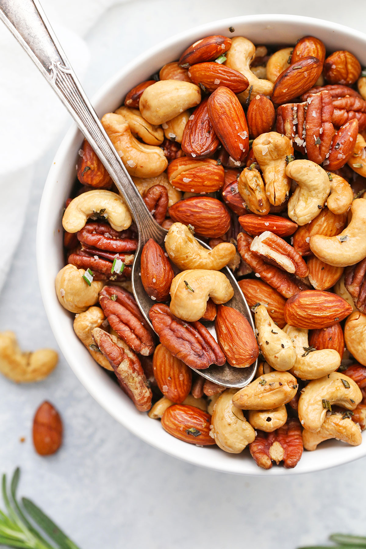 Close up overhead view of a bowl of Rosemary Sea Salt Mixed Nuts on a white background