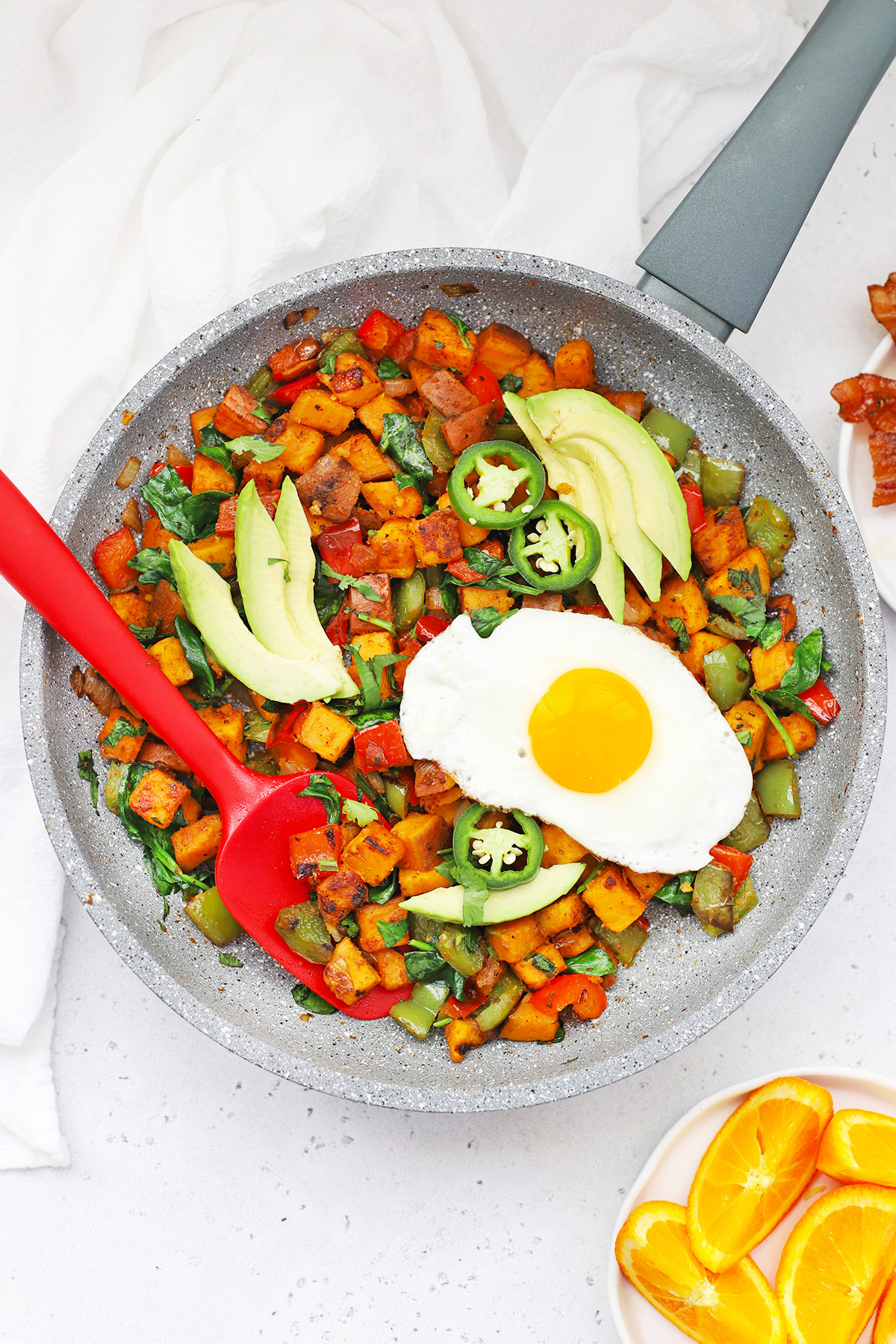 Overhead view of a pan of Paleo Southwest Sweet Potato Hash topped with sliced avocado, jalapeño, and an egg.