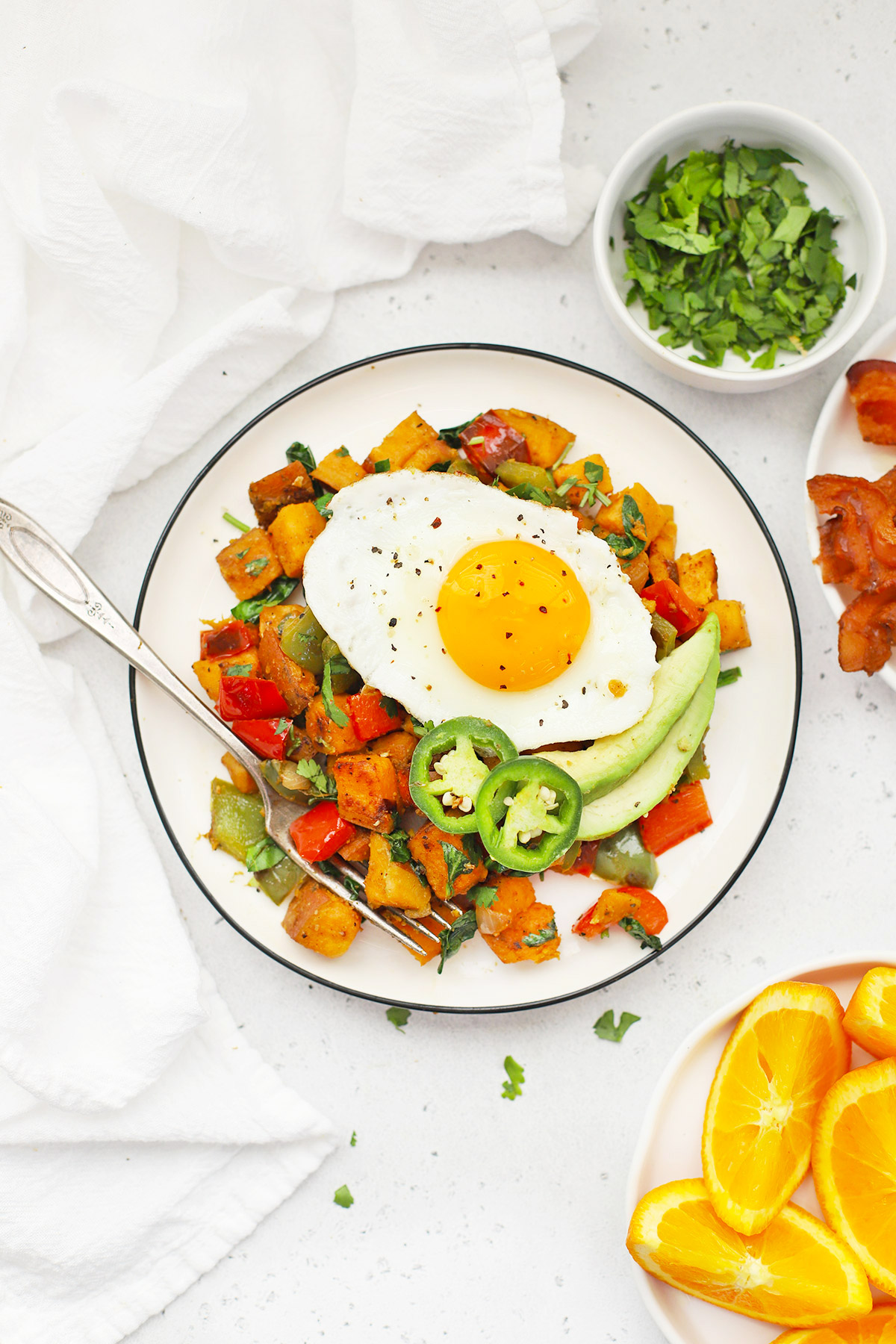 Overhead view of a plate of Southwest Sweet Potato Hash topped with an egg with plates of bacon and orange wedges on the side