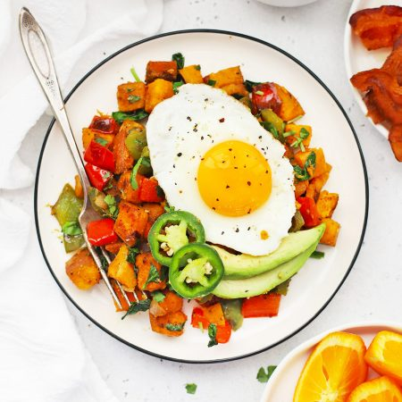 Close up Overhead view of a plate of Southwest Sweet Potato Hash topped with an egg with plates of bacon and orange wedges on the side