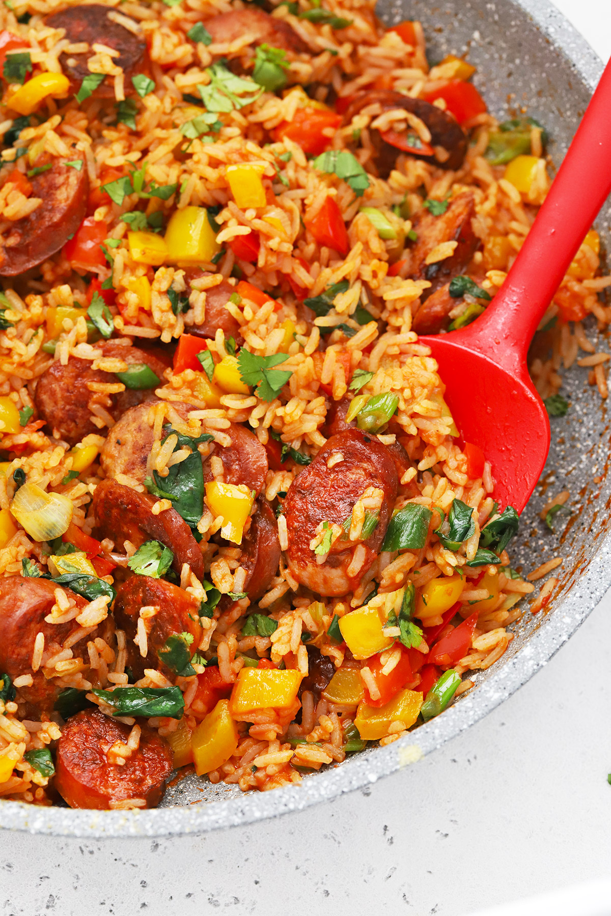Close-up overhead view of Cajun Sausage and Rice Skillet with a red spatula on a white background