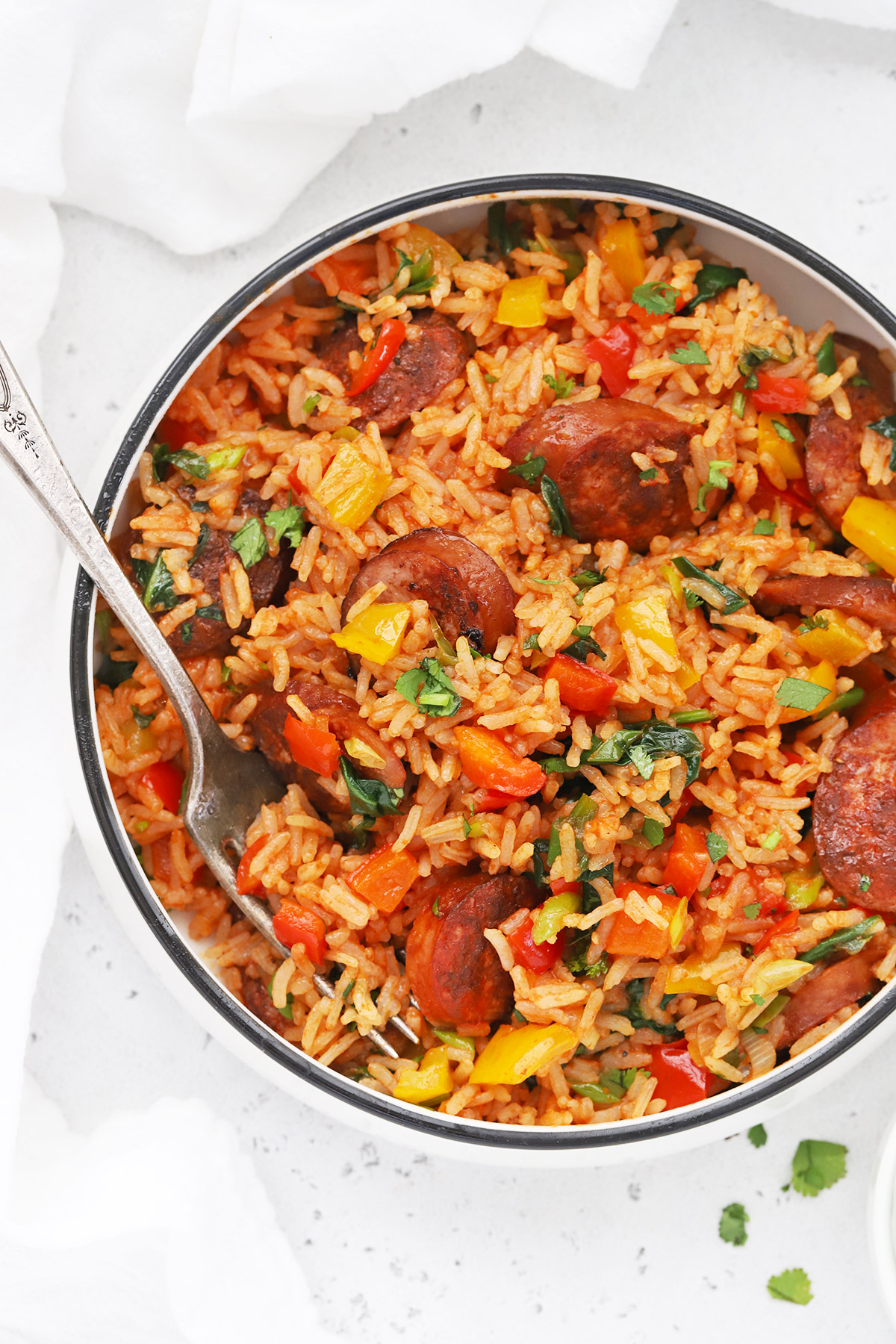 Close-up overhead view of a bowl of Cajun Sausage and Rice Skillet on a white background