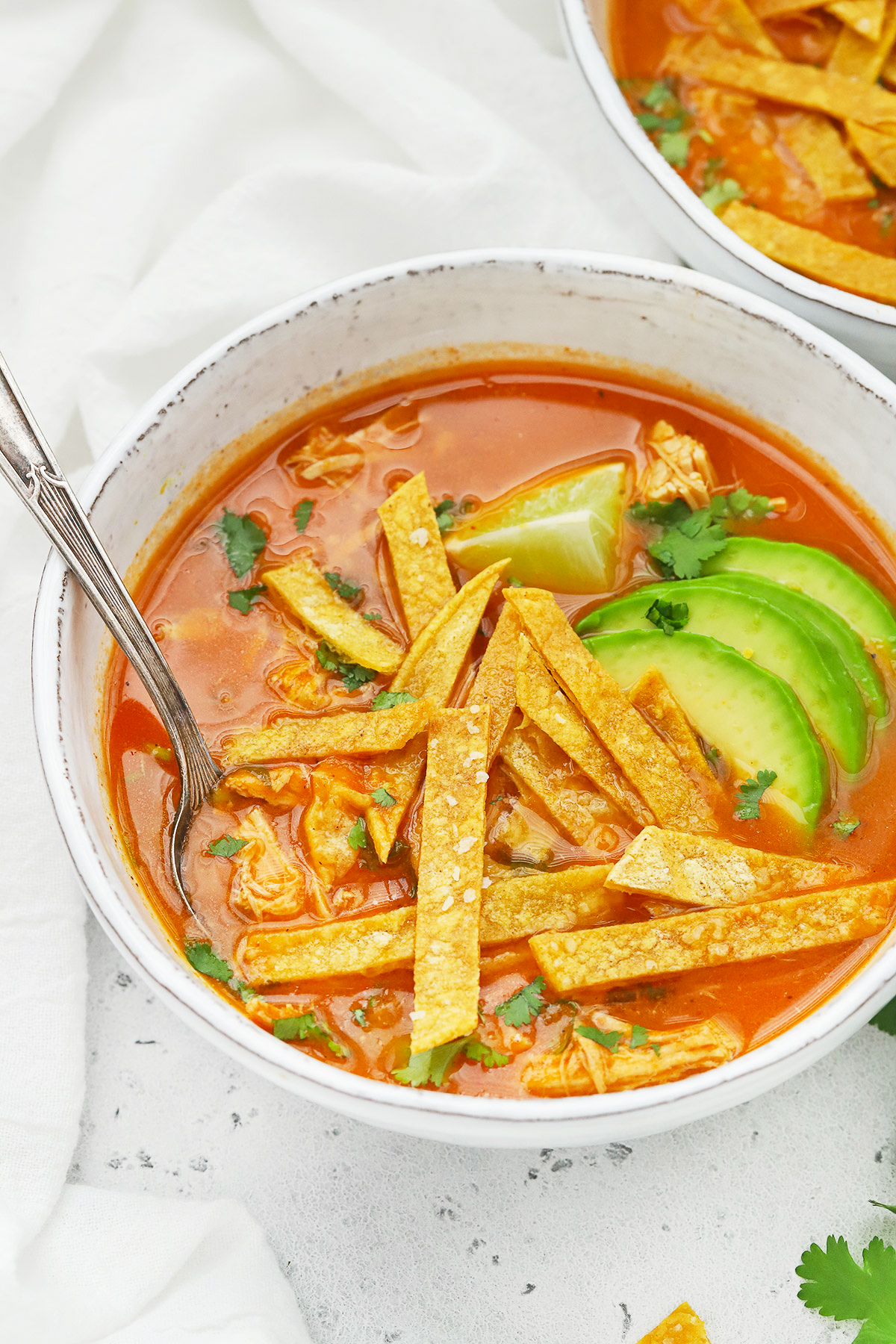 Front view of a white stoneware bowl of chicken tortilla soup topped with sliced avocado and crispy baked tortilla strips