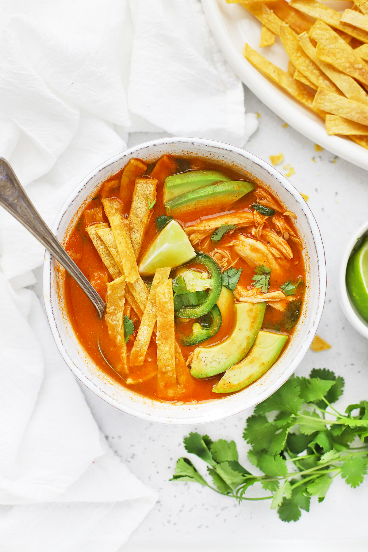 Overhead view of a white stoneware bowl of chicken tortilla soup topped with sliced avocado and crispy baked tortilla strips.