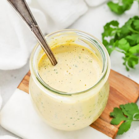 Front view of a jar of chipotle ranch dressing with a spoon in it.