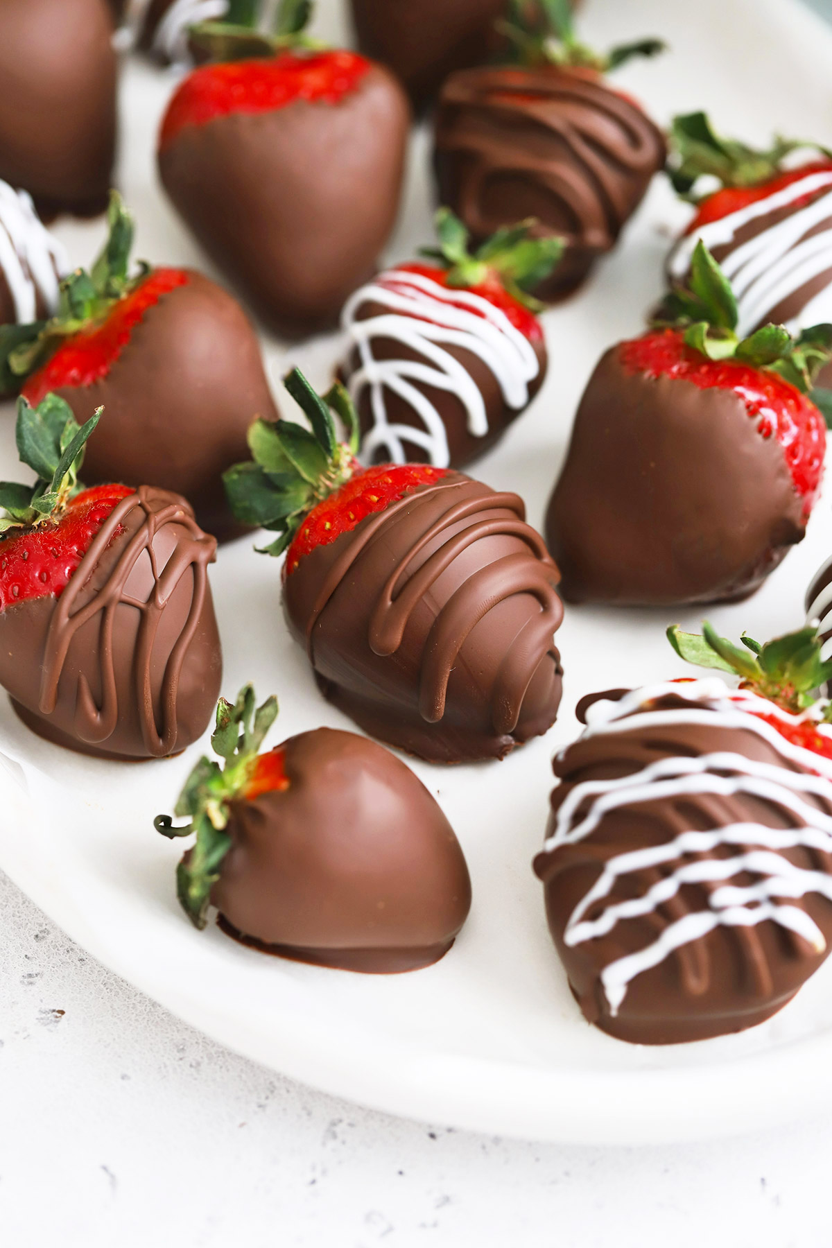 Close up Front view of vegan chocolate-covered strawberries on a white oval plate