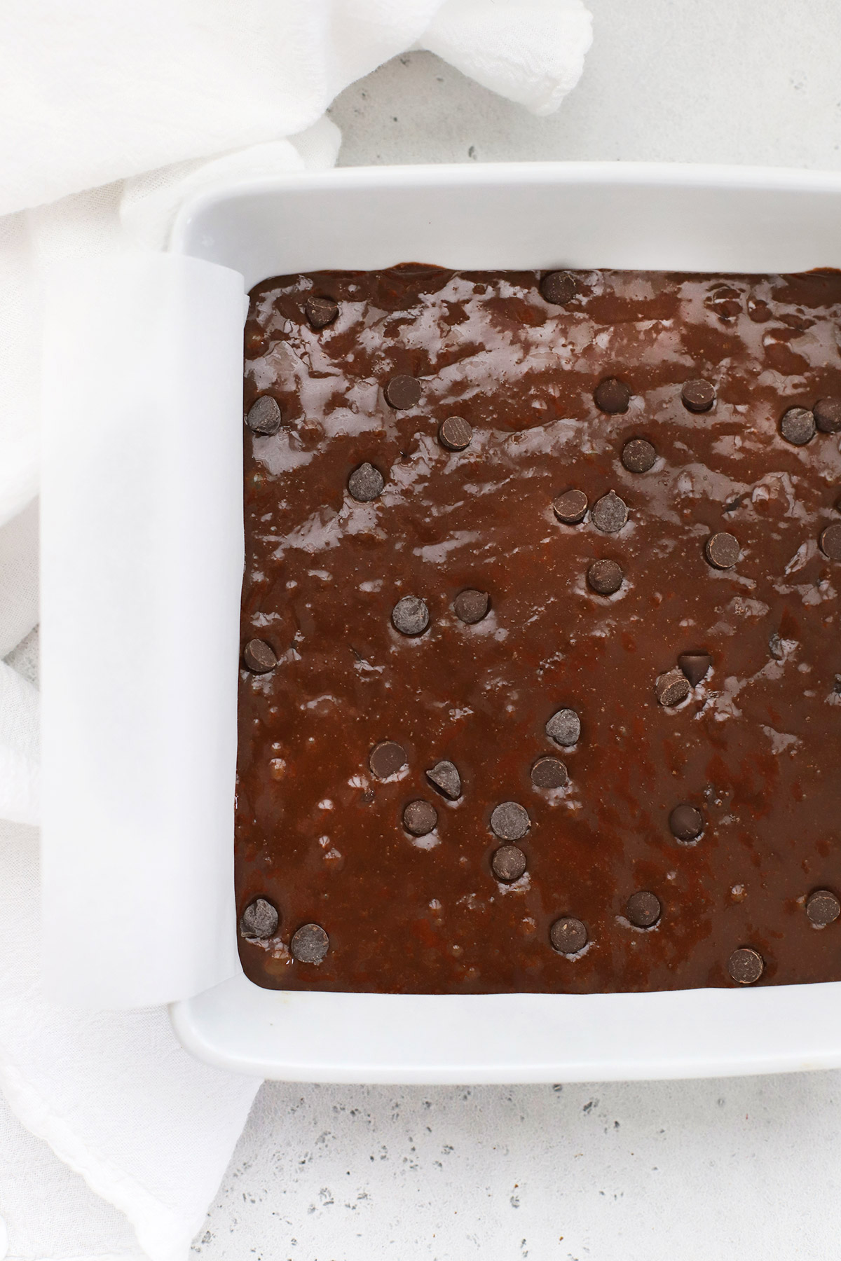 Overhead view of a white baking dish with gluten-free brownies ready to go into the oven