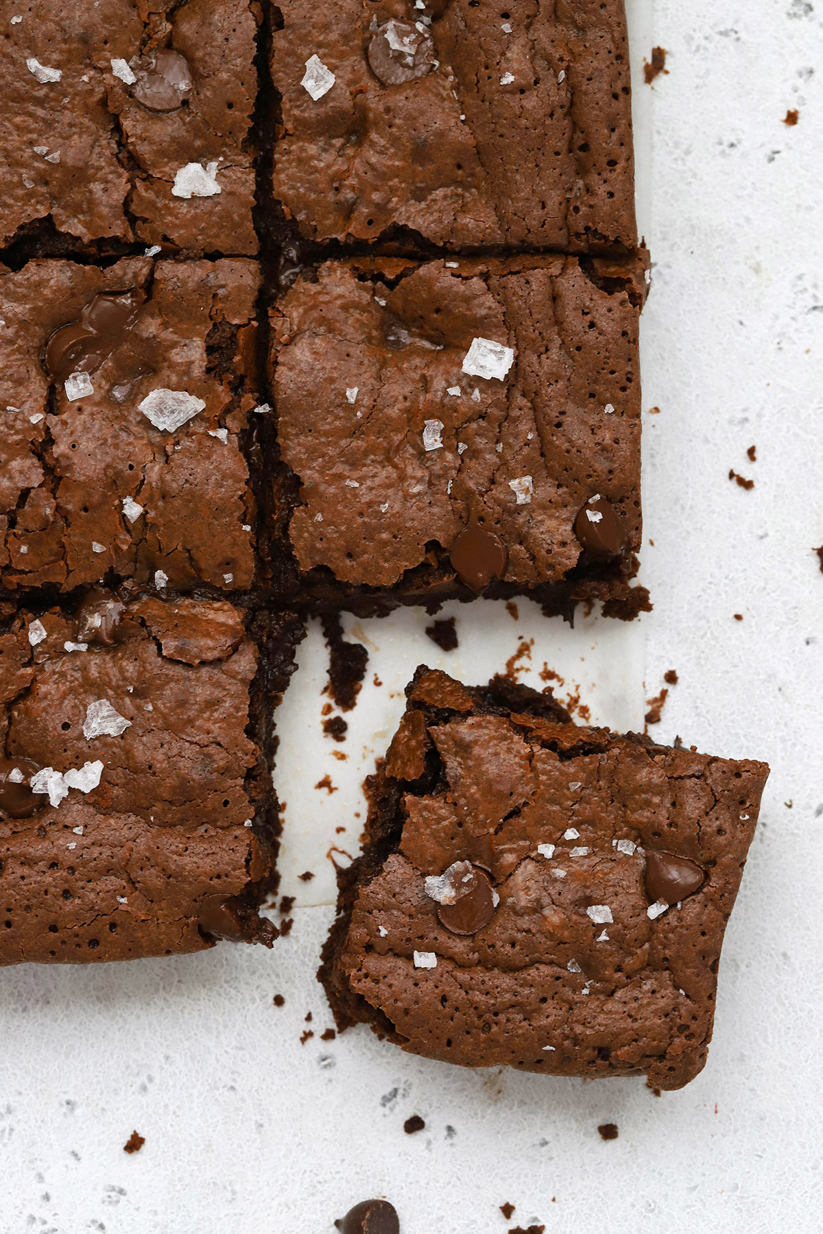 Close up overhead view of gluten-free brownies cut into squares and topped with sea salt.