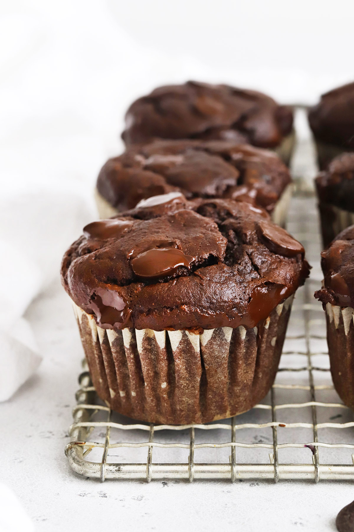 Close up front view of gluten-free chocolate banana muffins on a cooling rack