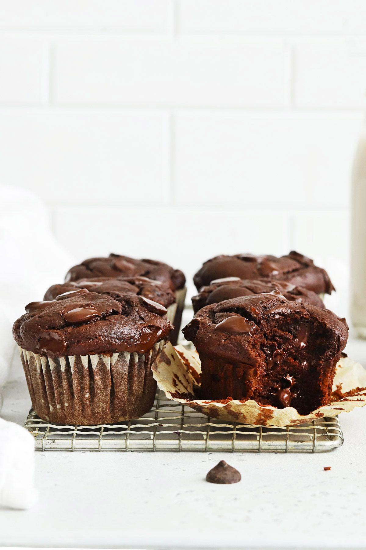 Front view of six gluten-free chocolate banana muffins on a cooling rack. One muffin is unwrapped with a bite taken out of it.