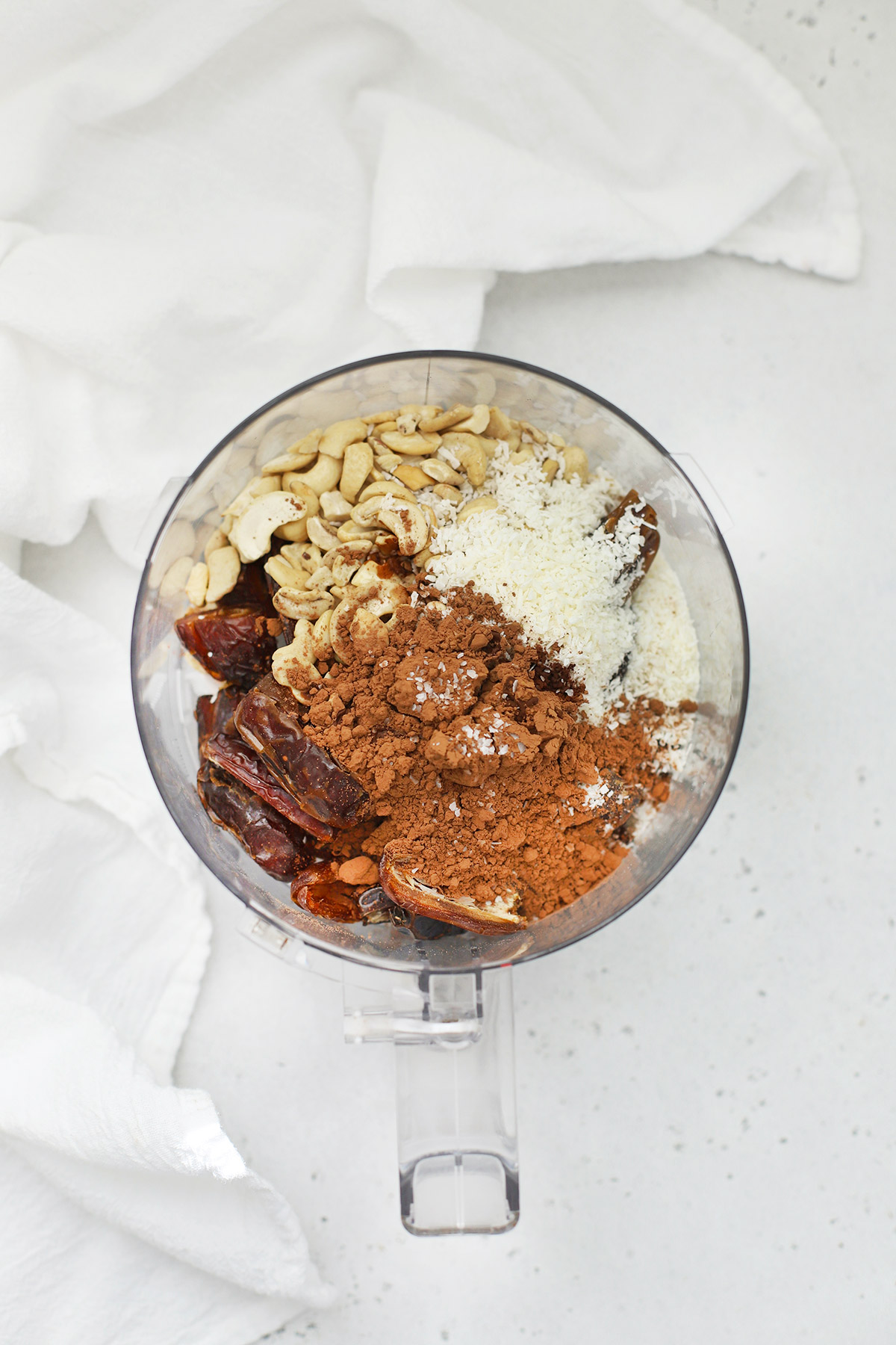 Overhead view of a food processor with ingredients for mint chocolate energy bites on a white background