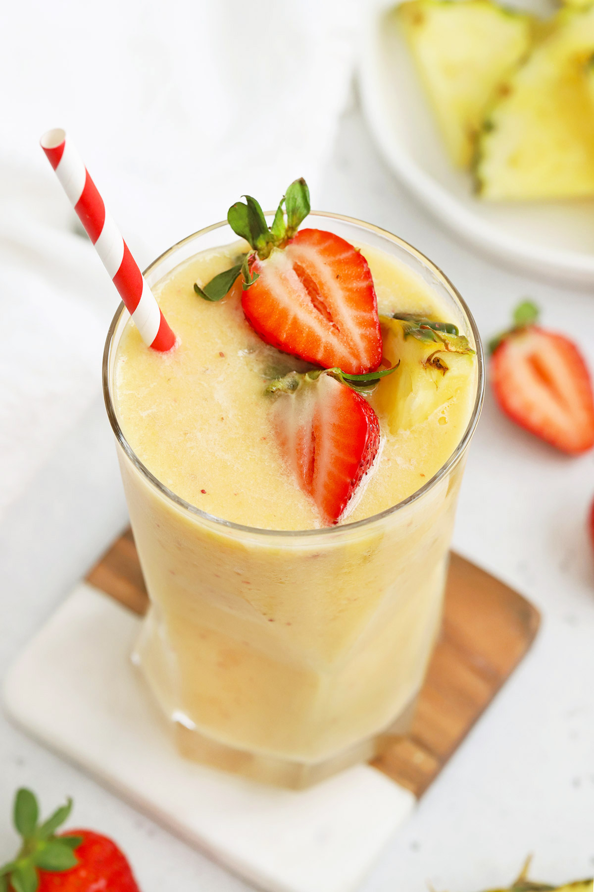 Glass of Strawberry Orange Sunrise Smoothie topped with fresh pineapple and strawberries with a red and white stripe straw