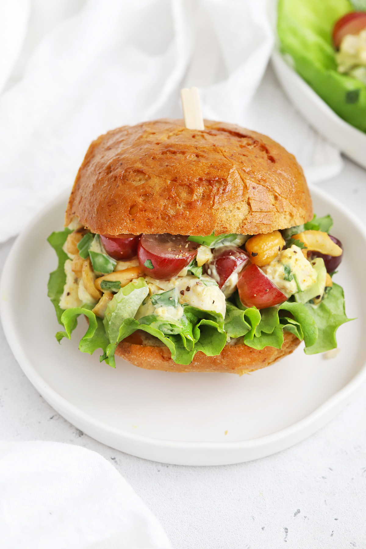 Close up Front view of a curry chicken salad sandwich with lettuce on a white background
