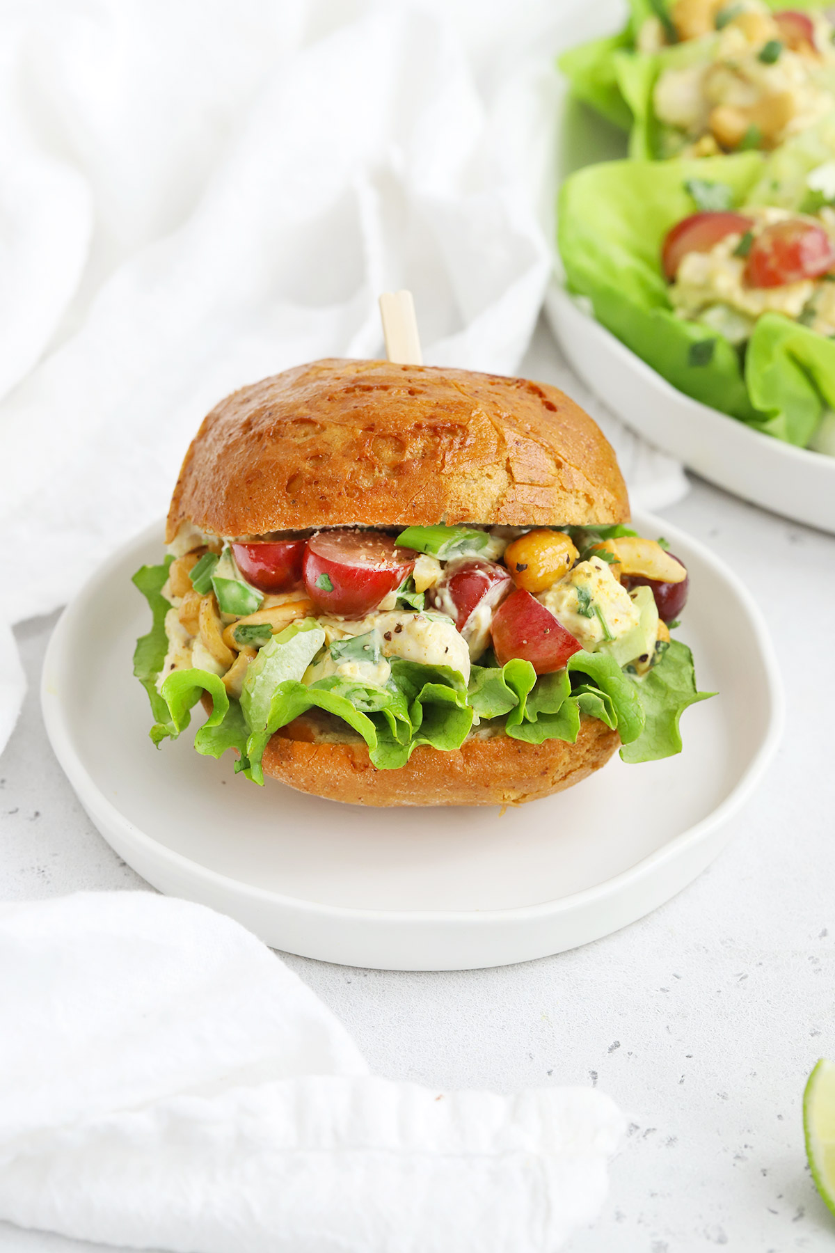 Front view of a curry chicken salad sandwich with lettuce on a white background