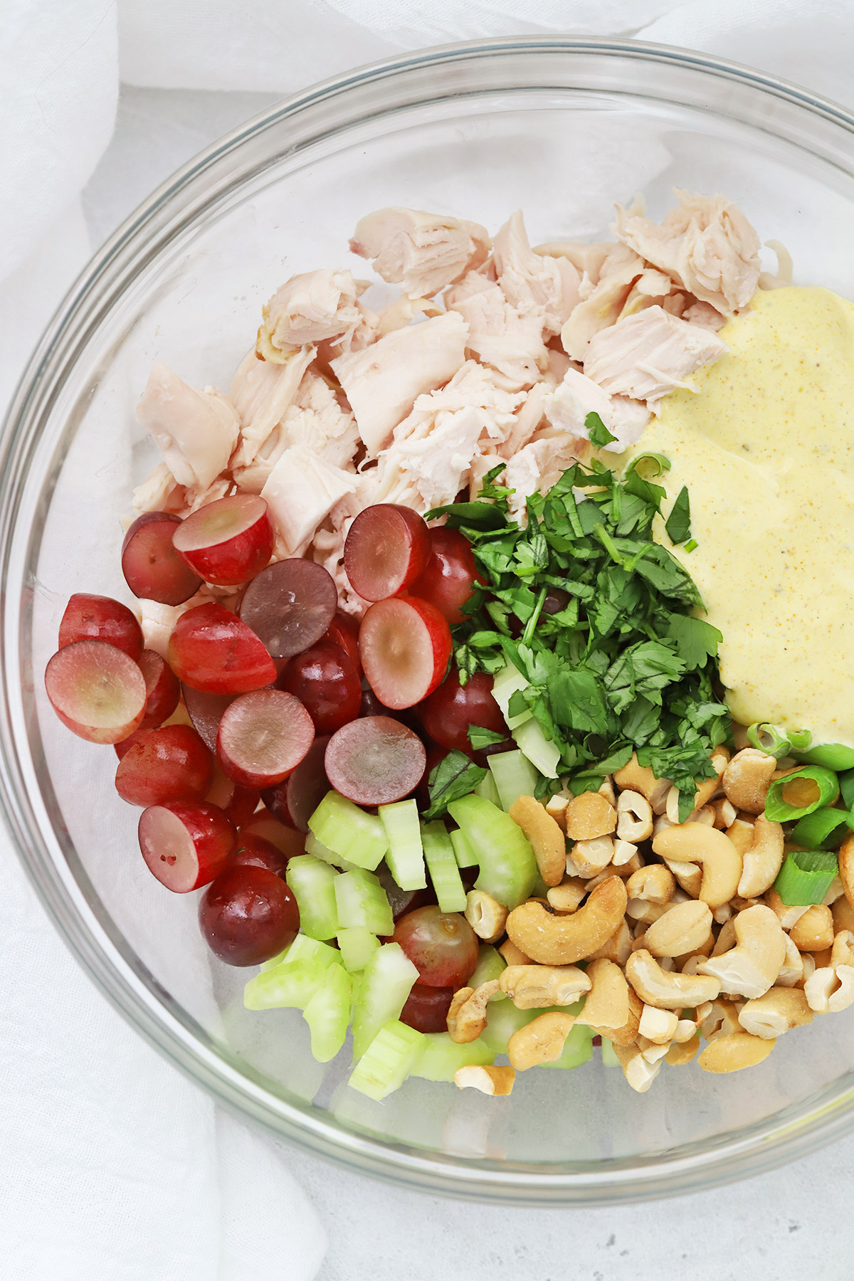 Close up overhead view of the ingredients for curry chicken salad ready to be mixed.