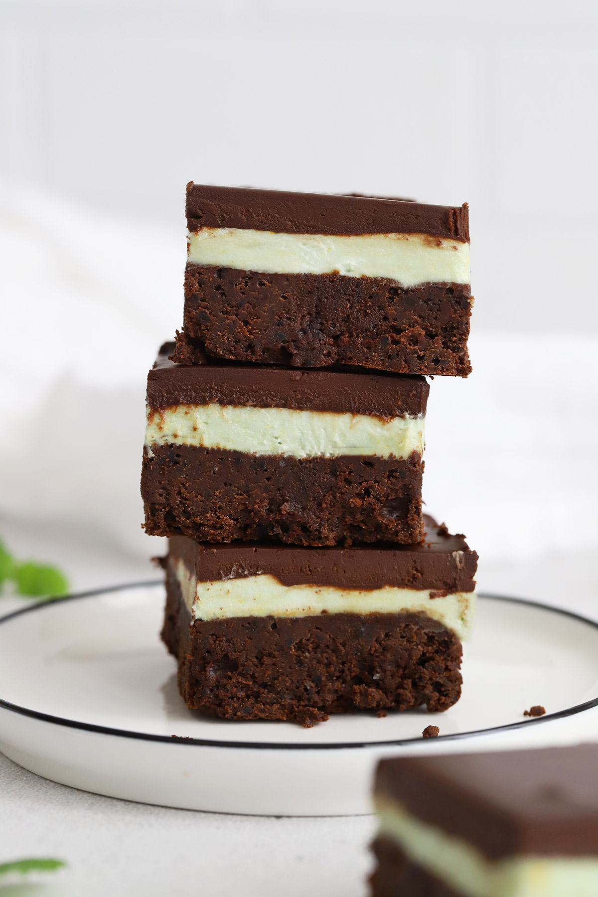 Front view of a stack of three gluten-free mint brownies on a white background