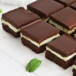 Overhead view of gluten-free mint brownie squares on a white background with fresh mint leaves scattered around