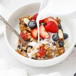 Front view of a slice of mixed berry baked oatmeal topped with fresh berries and sliced almonds with almond milk being poured on top