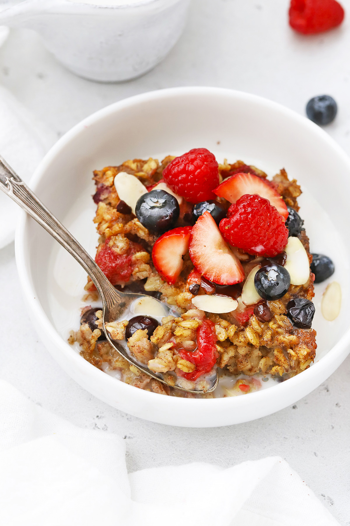 Front view of a slice of mixed berry baked oatmeal topped with sliced almonds, fresh berries and almond milk.