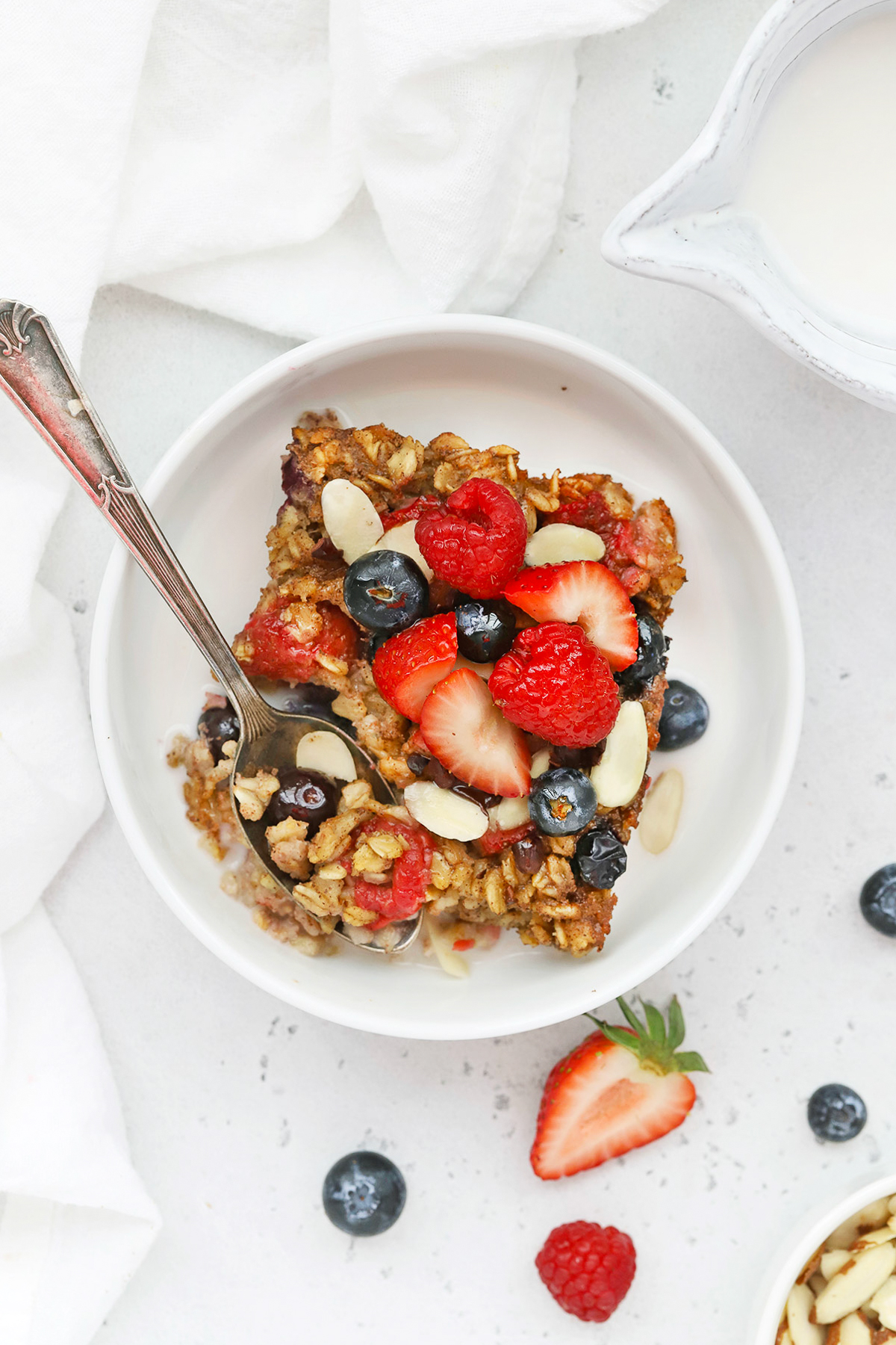 Overhead view of a slice of mixed berry baked oatmeal topped with fresh berries, sliced almonds, and almond milk on a white background