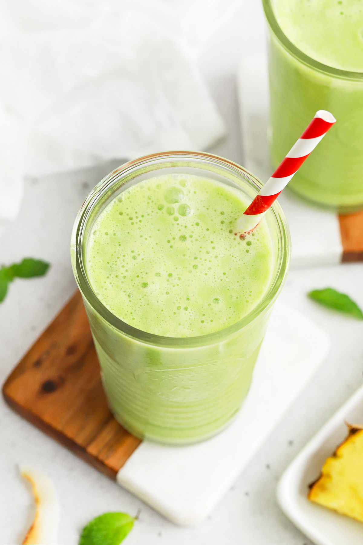 Close up Front view of a glass of pineapple mint smoothie with a red striped straw