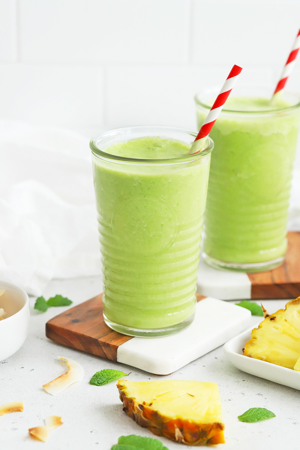 Front view of glasses of pineapple mint smoothie with red striped straws