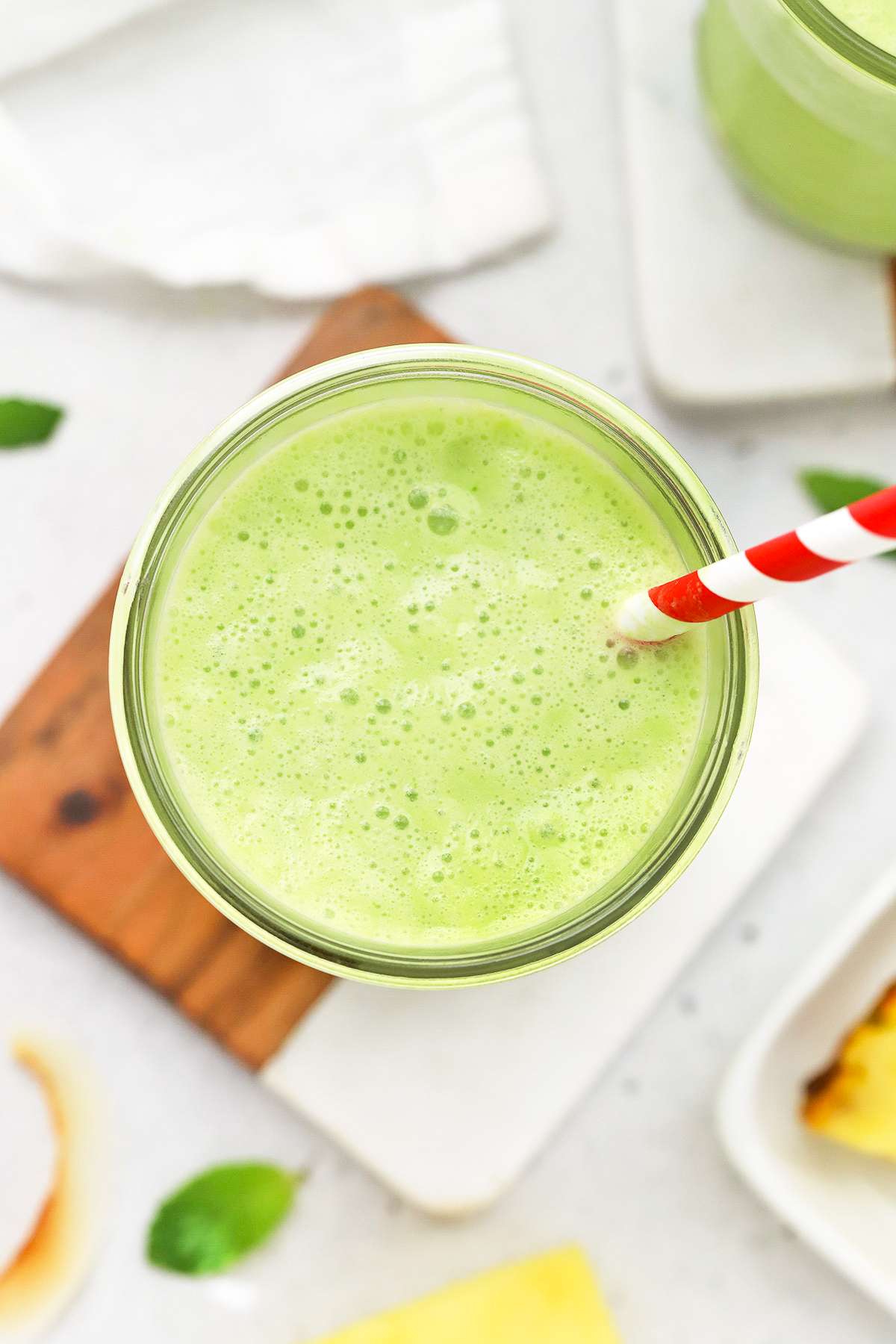 Close up overhead view of pineapple mint smoothie in a glass with a red striped straw