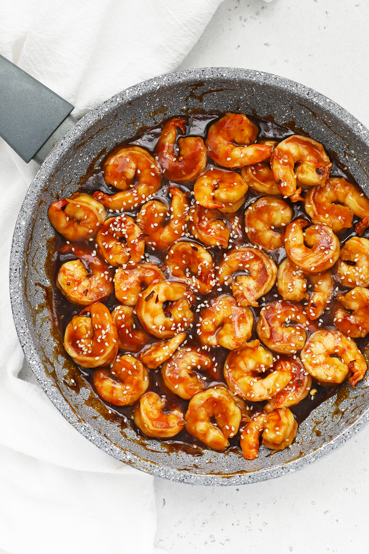 Overhead view of a pan of shrimp coated in sesame sauce