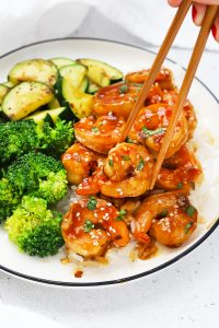 Front view of a plate of easy sesame shrimp with broccoli and zucchini