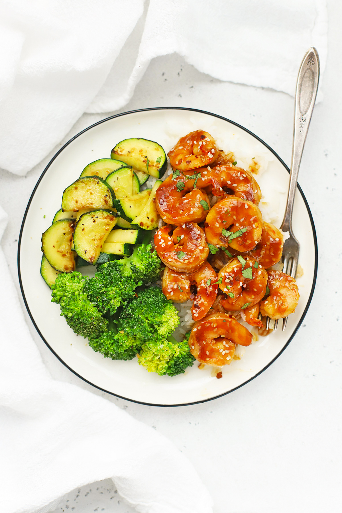 Overhead view of a plate of easy sesame shrimp with broccoli and zucchini on a white background