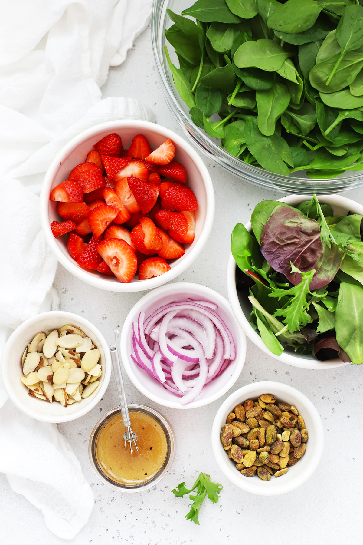 Overhead view of ingredients for strawberry spinach salad on a white background