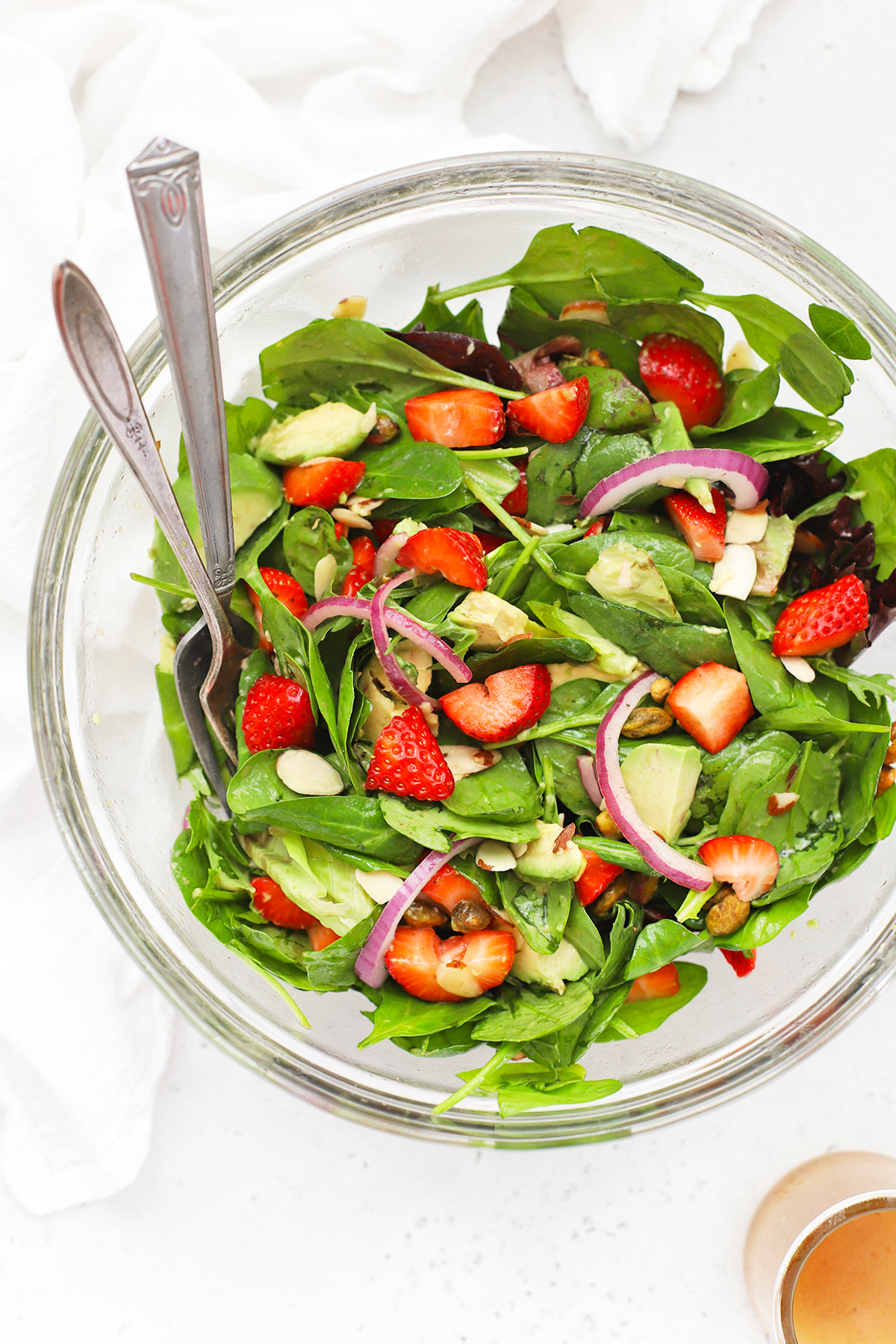 Overhead view of a mixing bowl of a tossed strawberry spinach salad