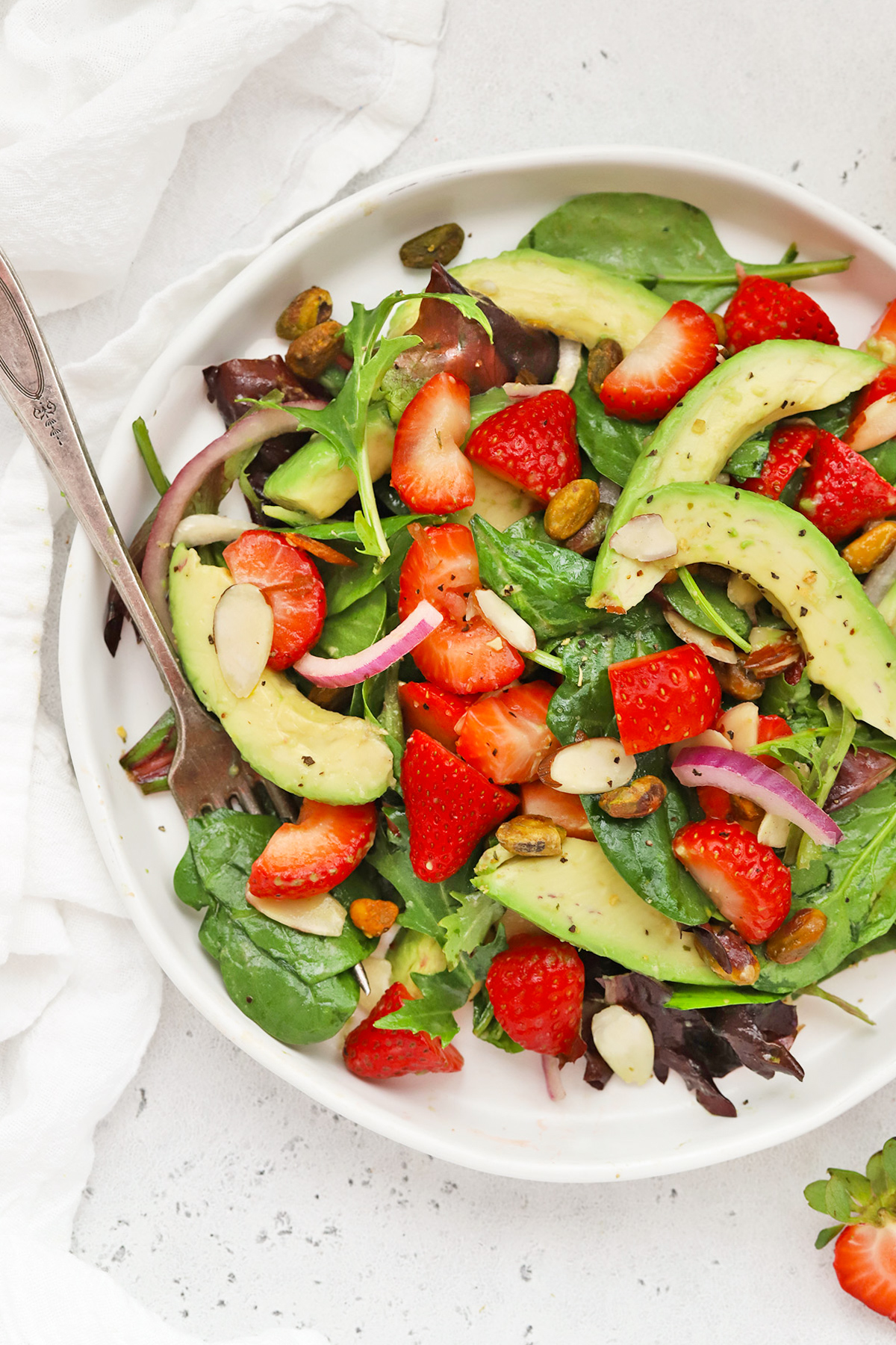 Overhead view of strawberry spinach salad on a white salad plate