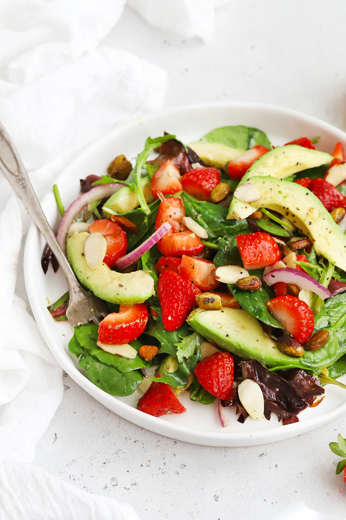 Front view of strawberry spinach salad with avocado on a white plate